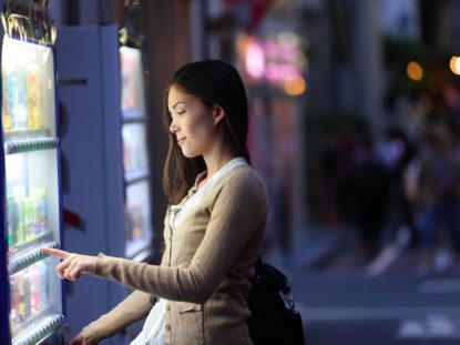 Frau zieht sich Getränk aus Automaten