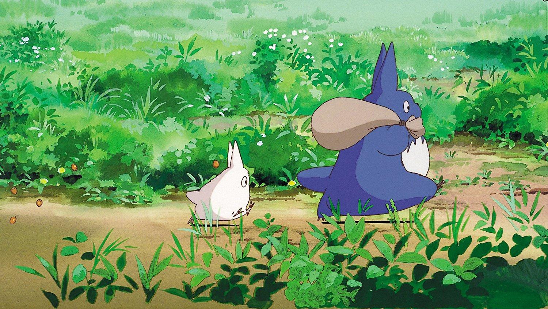 Totoro und ein Waldgeist gehen über eine Wiese